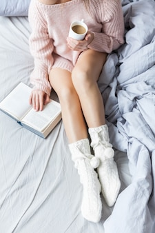 Woman resting keeping legs in warm socks on bed