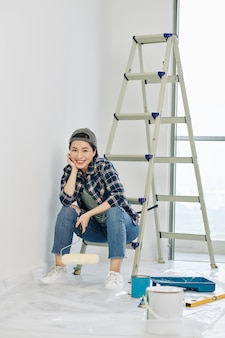 Woman resting on ladder after painting