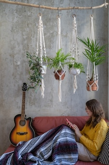 Woman resting lying on sofa under cotton macrame plant hanger with houseplants using cellphone