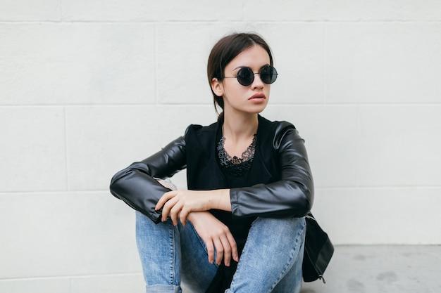 Женщина, сидящая рядом с белой стеной