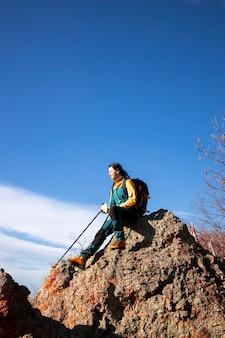 美しい屋外でのハイキング中に岩の上で休んでいる女性