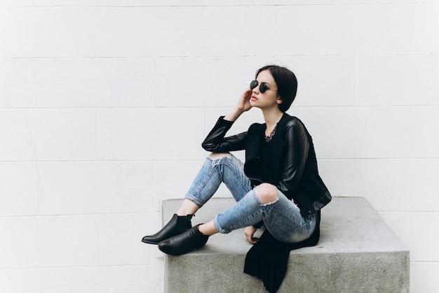Женщина, сидящая на цементном сиденье