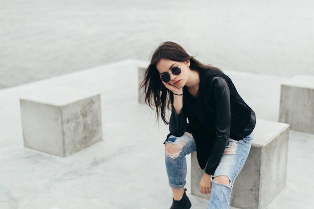 Женщина, покоится на бетонном кубе