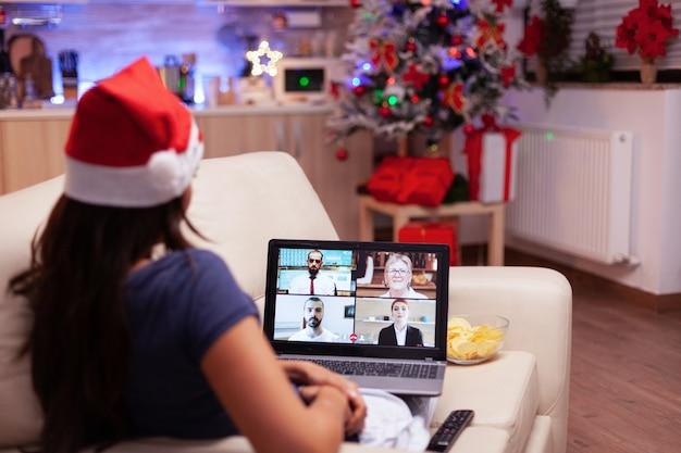 クリスマスを祝う離れた友人とリラックスしてソファで休んでいる女性