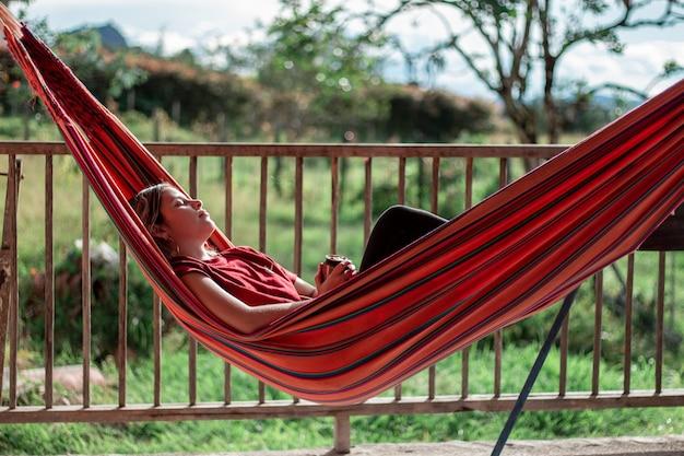 Женщина отдыхает в гамаке в окружении природы