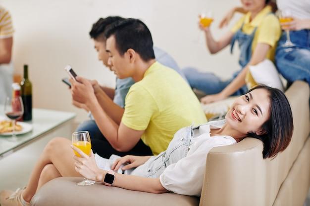 Женщина, отдыхая на диване на вечеринке