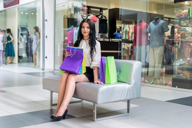 Женщина отдыхает на диване в торговом центре во время покупок