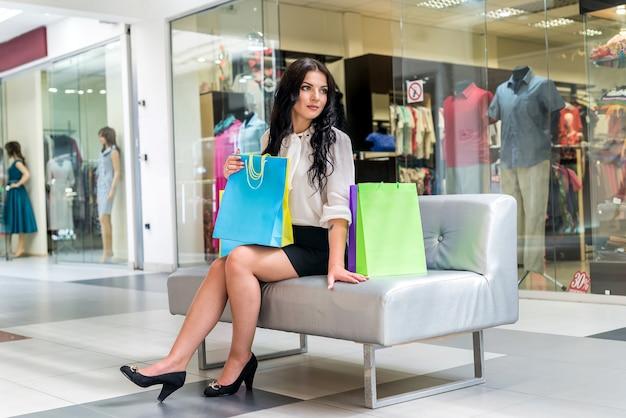 ショッピング中にモールのソファで休んでいる女性
