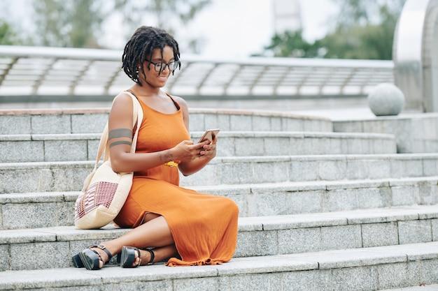 屋外の階段で休んでいる女性