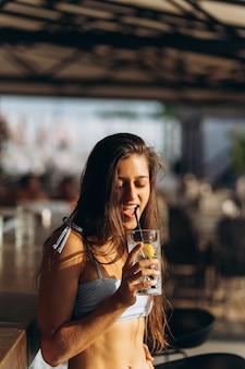 Женщина, отдыхая в баре на пляже, пьет освежающий коктейль