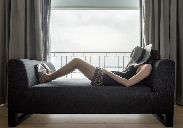 창문 옆 현대적인 소파에서 휴식을 취하는 여성
