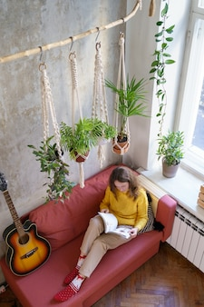 Woman resting, sitting on couch under cotton macrame plant hanger with houseplants, reading magazine