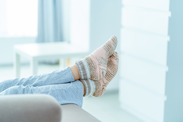 Woman resting on the sofa in pajamas and cozy soft comfortable knitted winter socks at home