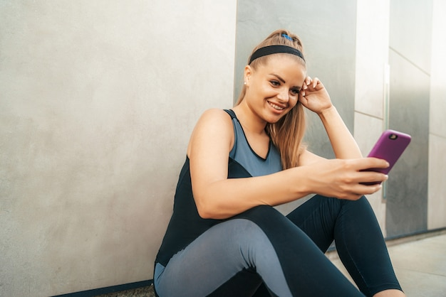 Woman resting in sportswear with smartphone
