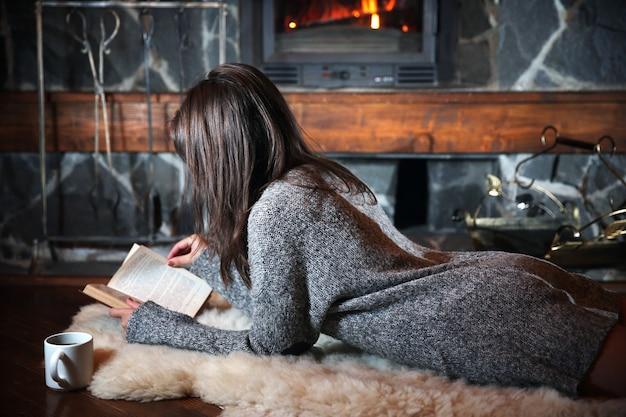 뜨거운 음료와 벽난로 근처 책 한잔과 함께 휴식하는 여자