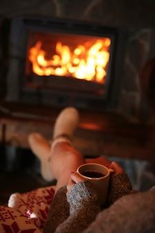 暖炉のそばで温かい飲み物を飲みながら休んでいる女性