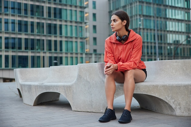 Woman rests after workout dressed in activewear and sneakers sits on gravestone uses wireless headphones for listening music focused away enjoys beautiful city view