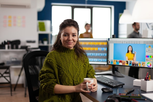 クリエイティブなデザインメディアエージェンシーに座って笑顔のカメラを見ている女性レタッチャー