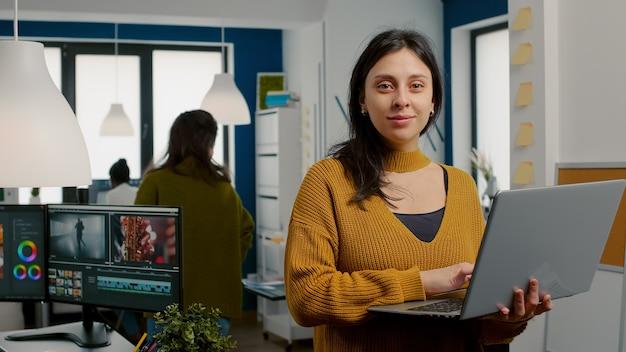 웹사이트 앞에 서 있는 크리에이티브 미디어 에이전시에서 일하는 카메라를 보고 웃는 여성 리터처