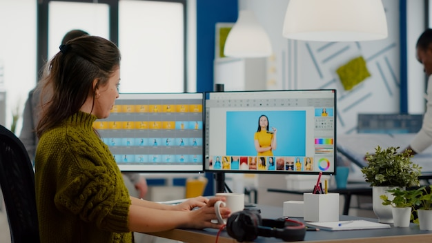 Woman retoucher looking at camera smiling sitting in creative media agency retouching client photos on pc with two displays