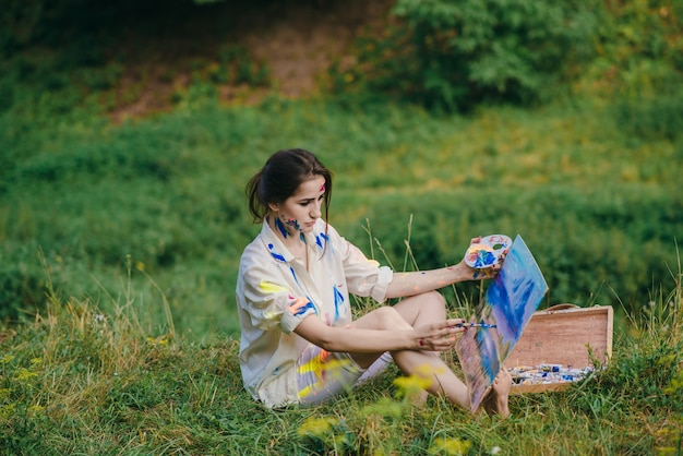 Woman retouching a picture sitting on the grass