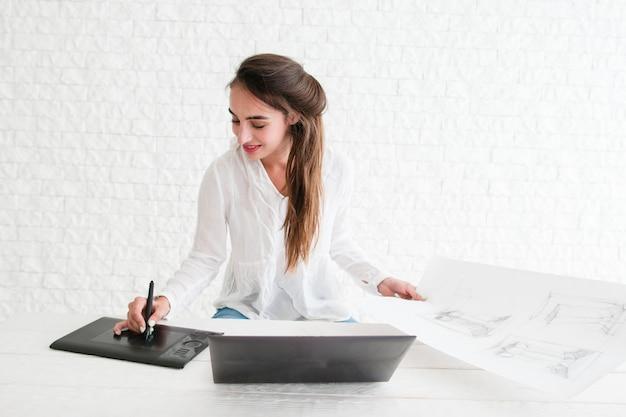 ノートパソコンでスケッチをレタッチする女性