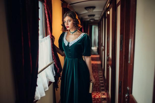 Woman in retro dress, vintage train compartment.
