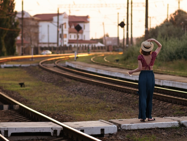 Woman in retro hat waving goodbye to the train.