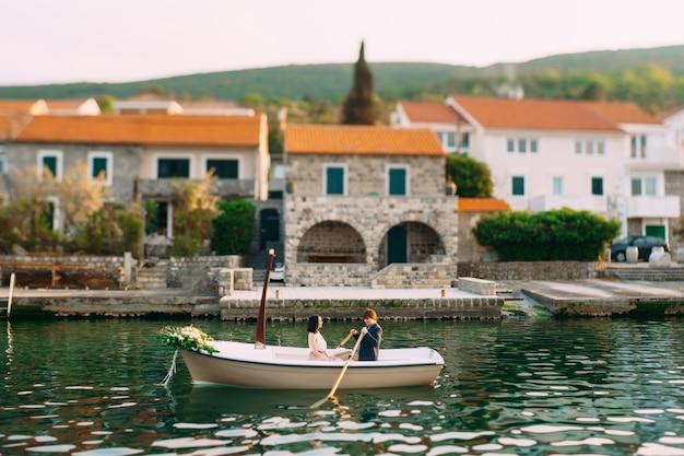 여자는 오래된 집이 있는 제방을 배경으로 노를 젓는 남자와 함께 배를 탄다
