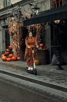 여자는 가을에 도시에서 전기 스쿠터를 탄다. 환경 친화적 인 개인 교통 수단 사용.