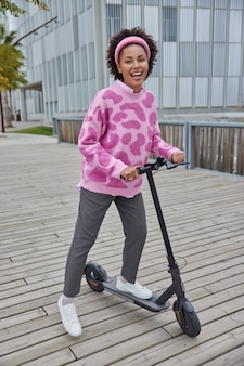 Woman rides electric scooter against urban background enjoys good day dressed in jumper trousers and sneakers has fun outdoors during sunny day