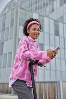 女性が街中の電動スクーターに乗るファッショナブルな服を着た幸せな表情は現代の電気輸送を使用し、オンラインのスマートフォンチャットは新しい場所を発見します