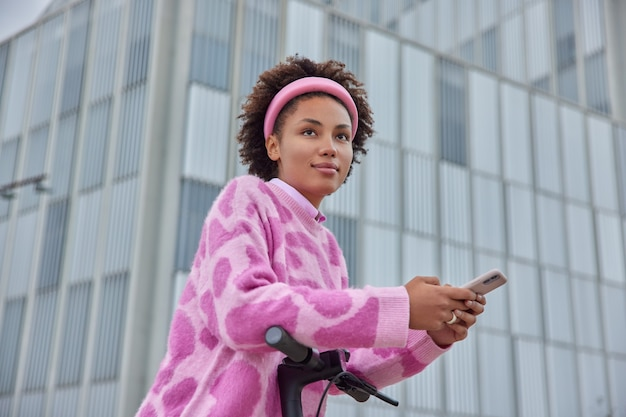 Woman rides electric scooter to work poses among office buildings uses smartphone for sending text messages dressed in casual jumper hoop on head focused forward