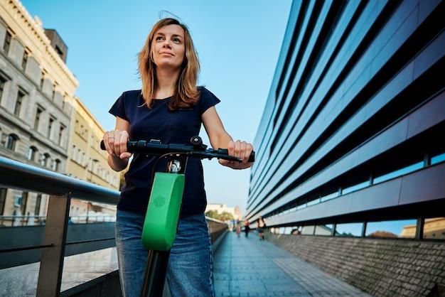 市内のレンタル電動スクーターに乗る女性