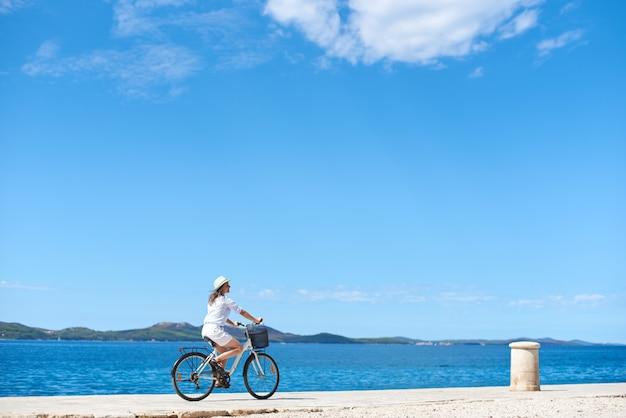 Женщина на велосипеде вдоль каменистого тротуара на синей игристой морской воде