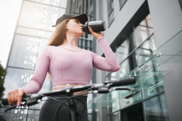 屋外の自転車に乗って、シェーカーから何かを飲む女性