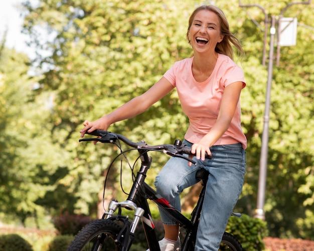 Женщина катается на велосипеде и смеется