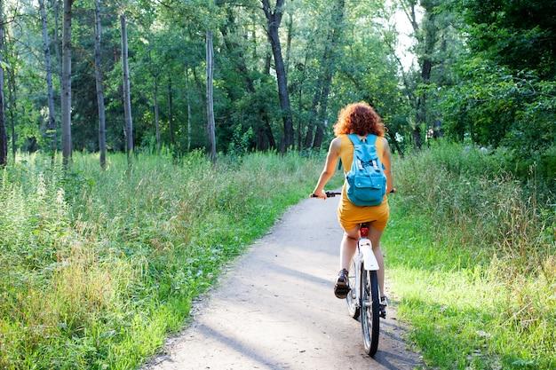녹색 숲에서 자전거를 타는 여자