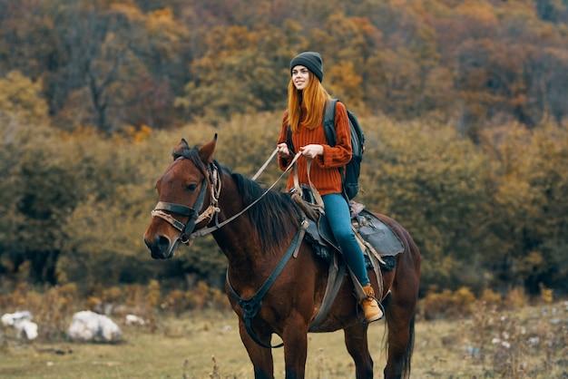 自然の山の旅の冒険に馬に乗る女性。高品質の写真