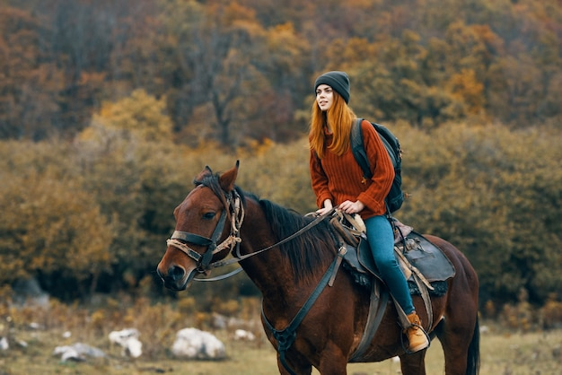 自然の山の旅の冒険に馬に乗る女性
