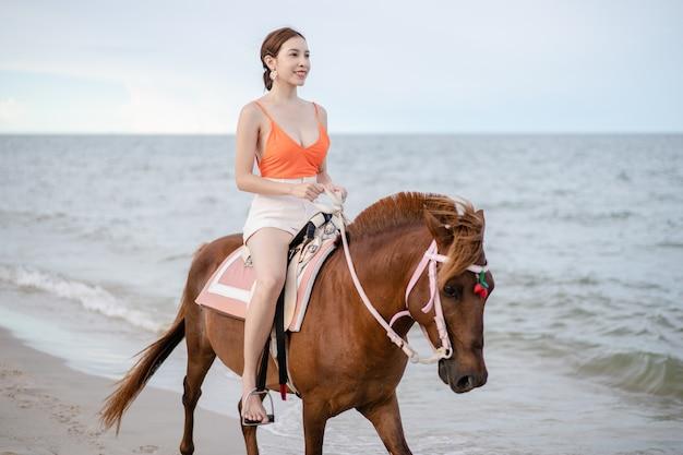 Женщина верхом на лошади на пляже утром.