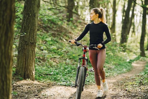 숲에서 산악 자전거를 타는 여자