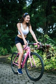 공원에서 자전거를 타는 여자. 핑크 자전거에 아름 다운 젊은 여자의 초상화입니다.