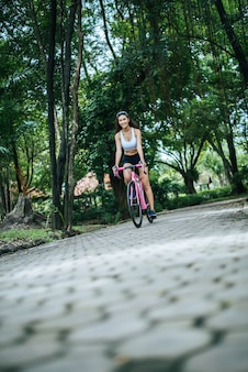 Woman riding a road bike in the park. Portrait of young beautiful woman on pink bike.
