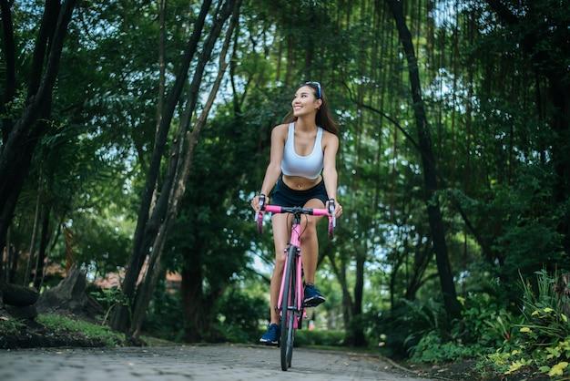 Женщина верхом на велосипеде в парке. портрет молодой красивой женщины на розовый велосипед.