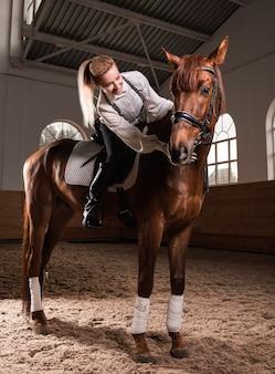 Женщина верхом на породистой лошади.