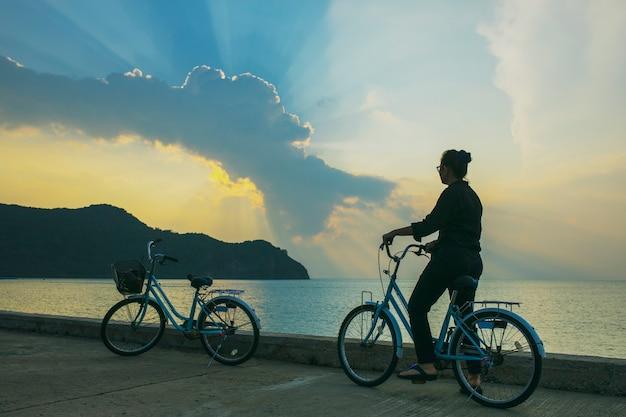 Женщина, езда на велосипеде на морской пирс против драматического солнечного света неба
