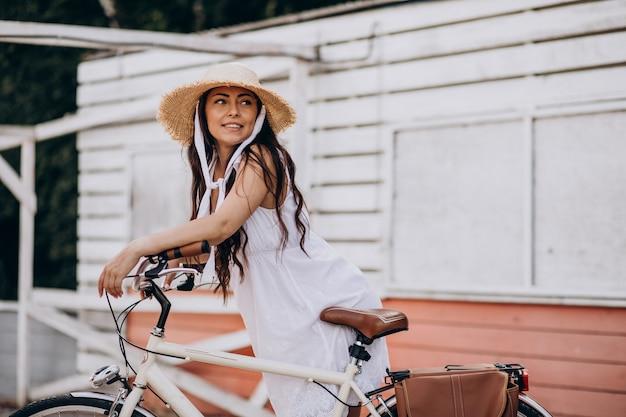 Женщина, езда на велосипеде в платье и шляпе