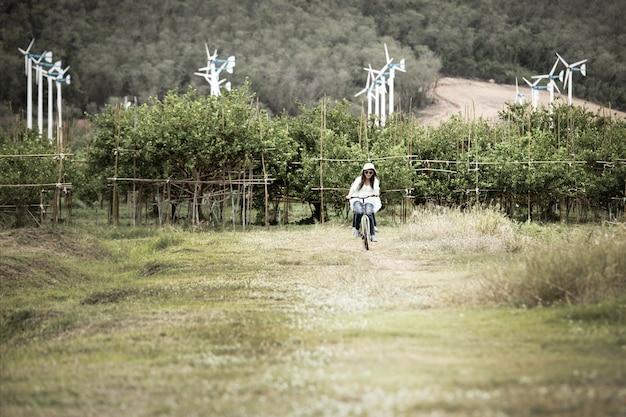Женщина, езда на велосипеде в поле с ветряной турбиной в винтажном стиле фона