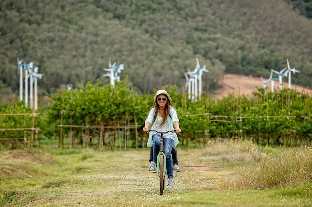 Женщина, езда на велосипеде в поле с ветряными турбинами в фоновом режиме